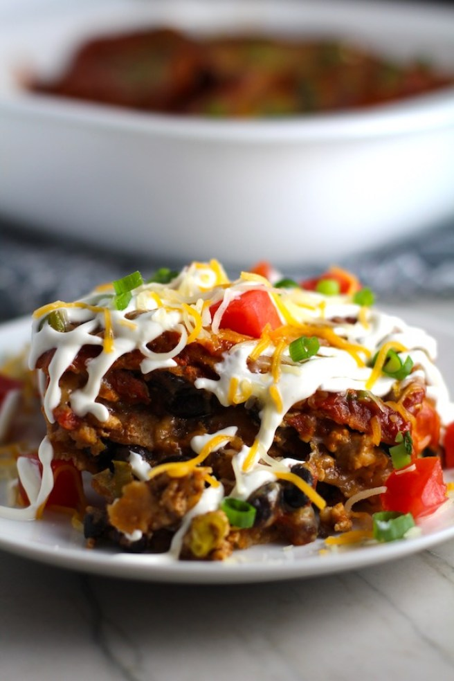 Close up side view of taco casserole piece on plate with sour cream drizzled on top and diced tomatoes and scallion on top. What could be better than tacos? A Taco Casserole that's made with healthier lean ground chicken and can be made ahead for your busy schedule. This Taco Casserole has corn tortillas layered with browned ground chicken seasoned with smokey mexican spices, black beans, tomatoes, and cheese, and then more cheese.