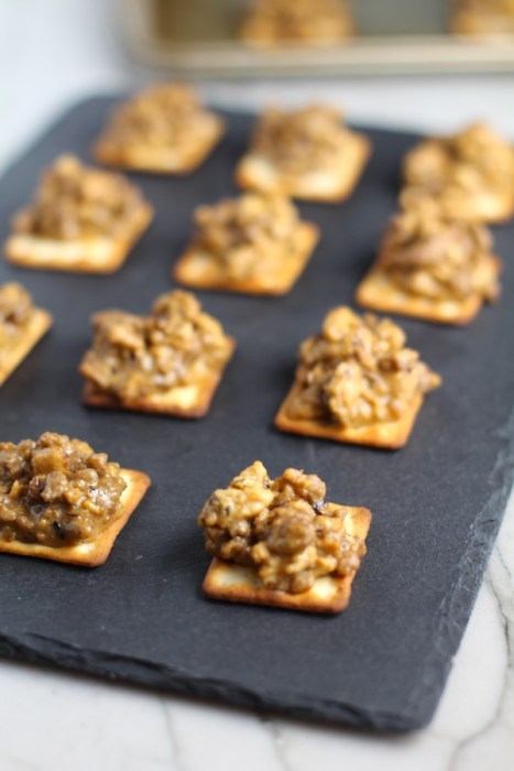 Cooked Hanky Panky on Black Slate Platter. These Hanky Panky Canapes are the BEST Party Appetizers around!  They cheesy, meaty, and absolutely delicious.  Ground Beef is mixed with Homemade Chicken Sausage and then combined with lots of cheese until its a creamy addictive pot of goodness.  Then it is scooped on top of bread, toasts, or crackers