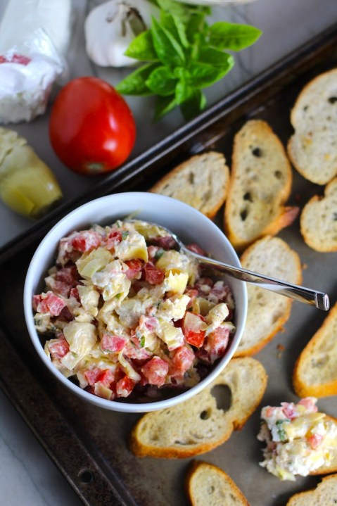 Bruschetta Topping in bowl on pan surrounded by crostini with ingredients to the left. It combines fresh tomatoes, artichoke hearts, garlic, basil, olive oil, and GOAT CHEESE!  Top on toasty garlic crostini and you get fresh bright flavors with both crunch and creamy in every bite.