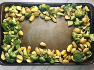 Potatoes and Broccoli around the outside of a sheet pan. This Flank Steak Recipe with Potatoes & Broccoli is an easy and delicious Sheet Pan Dinner.  It has a flavorful rub and a tangy, light Garlic Chive Crema!