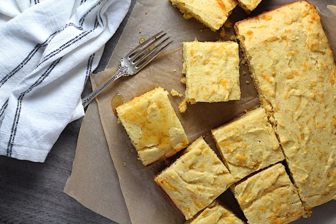 Cheddar Honey Gluten Free Cornbread pieces cut on parchment paper with honey drizzled on top and fork and crumbs around.