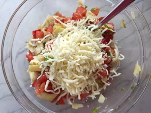 Tomato, artichoke, mozzarella in bowl for the Tomato Tart Recipe. It gives you crunch from the Quinoa crust, a burst of fresh from the tomatoes, tons of flavor from the basil and garlic, tang and meatiness from the artichoke and so much creaminess from the mozzarella and goat cheese! It's addictive and delicious!