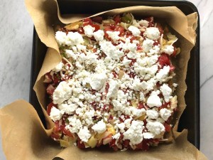 Quinoa crust Tomato, Artichoke, and goat cheese tart in pan with parchment paper for the Tomato Tart Recipe. It gives you crunch from the Quinoa crust, a burst of fresh from the tomatoes, tons of flavor from the basil and garlic, tang and meatiness from the artichoke and so much creaminess from the mozzarella and goat cheese! It's addictive and delicious!