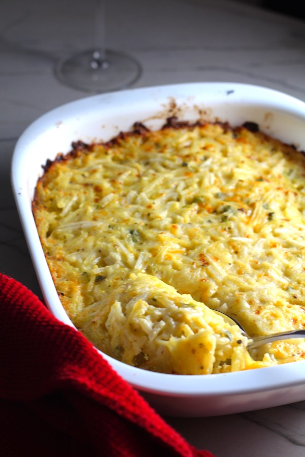 Spoon scooping Cheesy Hash Brown Casserole in casserole dish on counter with red towel. This recipe does not disappoint! It's warm, creamy, and full of flavor! And it's the perfect side dish for your holiday dinner.