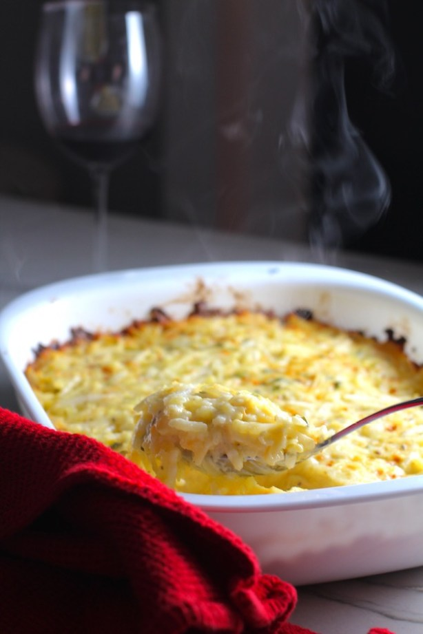 Spoon scooping Cheesy Hash Brown Casserole in casserole dish on counter with wine glass in background. This recipe does not disappoint! It's warm, creamy, and full of flavor! And it's the perfect side dish for your holiday dinner.