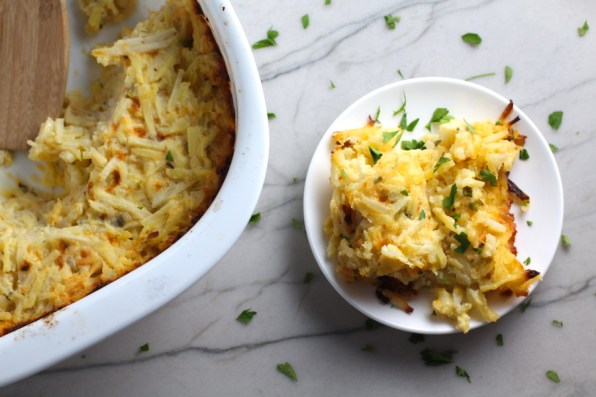Cheesy Hash Brown Casserole on plate and in casserole dish on counter. This recipe does not disappoint! It's warm, creamy, and full of flavor! And it's the perfect side dish for your holiday dinner.