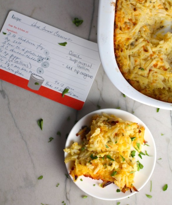 Cheesy Hash Brown Casserole on plate and in casserole dish on counter with recipe card. This recipe does not disappoint! It's warm, creamy, and full of flavor! And it's the perfect side dish for your holiday dinner.