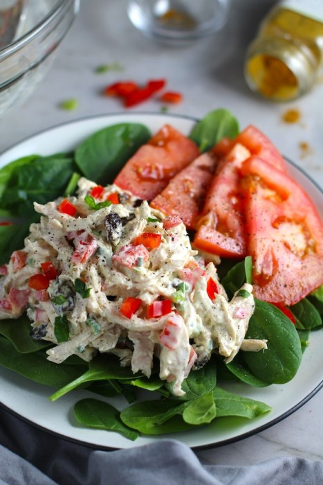 Curry Chicken Salad on spinach with tomato slices. It has so many fantastic flavors and textures!  The chicken breast is simply roasted and mixed with a creamy sweet and savory curry dressing.  Red pepper gives you a fresh crunch, scallion gives a savory bite, and raisins give a burst of sweet.  #chicken #chickenrecipes #chickensalad #currychicken #mealprep #lunch #healthyrecipes