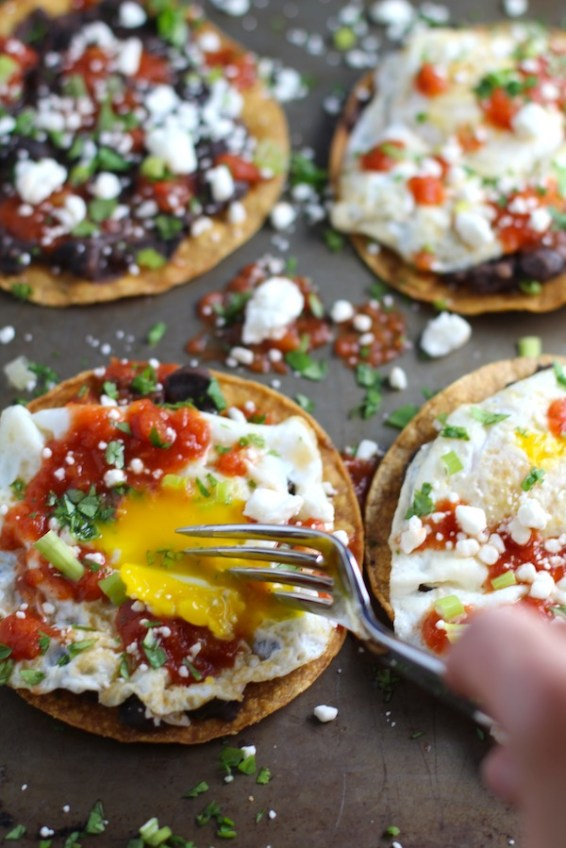 Huevos Tostadas are utterly delicious! They are similar to the better known Huevos Rancheros but are a pick up and eat with your hands version! They have crispy corn tortillas topped with creamy mashed black beans, a salty fried egg, smoky tomato sauce, cheese, and scallions! #huevosrancheros #eggs #brunch #mexicanrecipes #vegetarian #meatlessrecipes