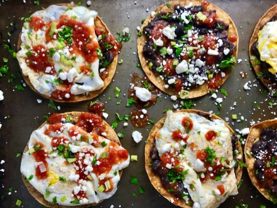 Huevos Tostadas are utterly delicious! They are similar to Huevos Rancheros but are a pick up and eat with your hands version! They have crispy corn tortillas topped with creamy mashed black beans, a salty fried egg, smoky tomato sauce, cheese, and scallions! #huevosrancheros #eggs #brunch #mexicanrecipes #vegetarian #meatlessrecipes