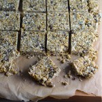 No Bake Energy Bites on parchment and cut into squares. These Easy Nut-Free, No-Bake Energy Bites with Chocolate Chips are magnificent!  They are sweet, chewy, crunchy, & healthy.  Only minutes to make & no Baking! Breakfast, snack, or dessert. #energybars #granolabars #snackrecipes #healthyfood #healthyrecipes #healthysnacks #healthybreakfast #healthydessert