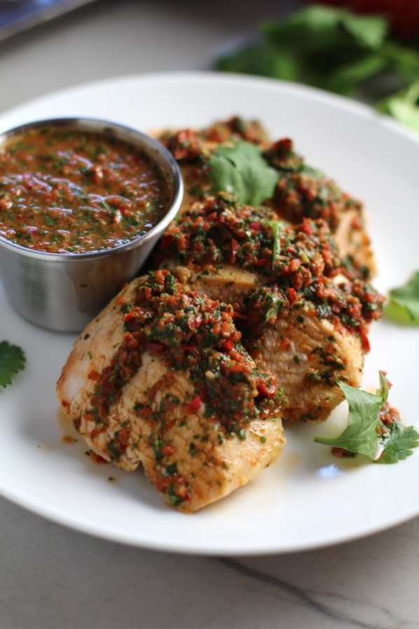 Chicken Chimichurri Rojo on a plate with cup of chimichurri. It is broiled or grilled Chicken topped with a cool, fresh, tangy, and incredibly full-flavored!  The Rojo comes from the addition of red pepper.  All of the ingredients simply get blended in a food processor so it could not be easier!  #chicken #chickenrecipes #chimichurri #easychicken #easydinners #dinner