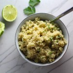 Cilantro Lime Quinoa in a bowl with spoon with lime and cilantro on counter. It's fluffy, nutty, citrusy, salty, and the perfect accompaniment for any protein or vegetable!  With just a few simple ingredients, you can make this fantastic healthier alternative to rice. #quinoa #quinoarecipes #sides #healthyfood