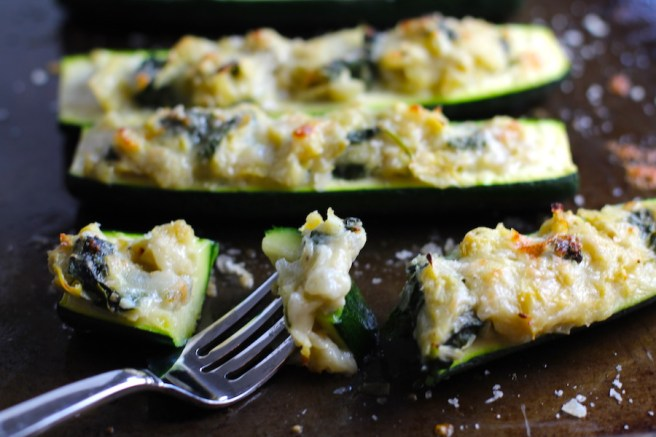 Fork with bite of Spinach Artichoke Stuffed Zucchini on a pan. Each fantastic bite gives you creamy artichoke, nutty cheesy Parmesan, spinach, and zucchini. Prepare entirely ahead, then bake 20 minutes and enjoy! #vegetarian #zucchini #stuffedzuchini #spinach #artichoke #springrecipes #healthyfood #healthydinner #healthyrecipes #glutenfree