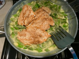Chicken added to asparagus sauce in pan for Lemon Dill Sauce Chicken and Asparagus. It has chicken in a light and creamy sauce flavored with garlic, lemon and fresh dill. It's loaded with fresh asparagus. #springrecipes #dinner #easydinner #healthydinner #lemon #asparagus #chicken #glutenfree #easyrecipes