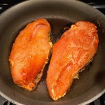 Hungarian Paprika Chicken raw cooking in a skillet. The paprika gives beautiful color and a deep, peppery flavor. #chicken #easychicken #easydinner #dinner #healthydinner