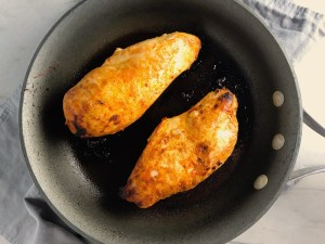 Hungarian Paprika Chicken cooking in a skillet. The paprika gives beautiful color and a deep, peppery flavor. #chicken #easychicken #easydinner #dinner #healthydinner