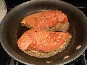 Raw Chicken getting seared in skillet for Sesame Sweet Chili Chicken recipe. It is slightly sweet, tangy, savory, nutty, with a touch of heat. You can prepare it days ahead, it takes just minutes to prepare, minutes to cook, and everyone will love it!! #chicken #marinades #easydinner #easychicken #chickenrecipes #easysauces #healthydinner #healthyfood #healthyrecipes