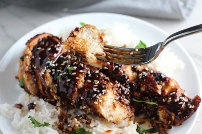 Bite of Sesame Sweet Chili Chicken on a fork over more sliced on a plate with rice. It is slightly sweet, tangy, savory, nutty, with a touch of heat. You can prepare it days ahead, it takes just minutes to prepare, minutes to cook, and everyone will love it!! #chicken #marinades #easydinner #easychicken #chickenrecipes #easysauces #healthydinner #healthyfood #healthyrecipes