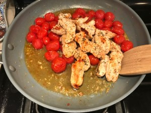 Chicken and Cherry tomatoes cooking in skillet for Chicken and Cherry Tomato Pasta with basil and parmesan. It's easy and so delicious! #pasta #tomatoes #easydinner #dinner #easyrecipes #healthydinner #chicken