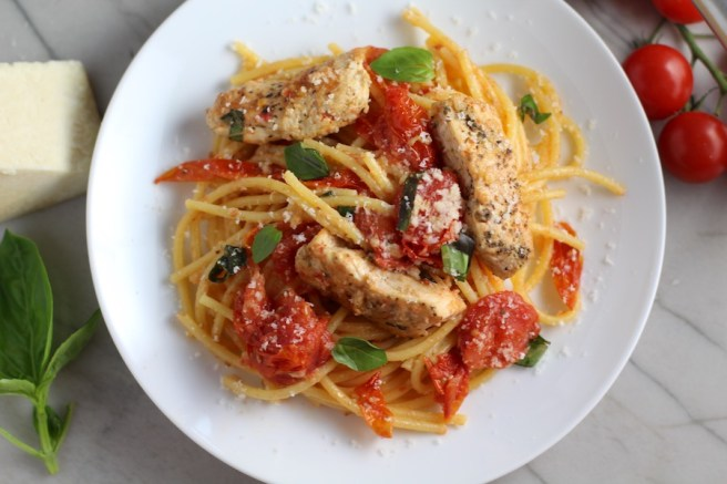Chicken and Cherry Tomato Pasta with basil and parmesan on a plate. It's easy and so delicious! #pasta #tomatoes #easydinner #dinner #easyrecipes #healthydinner #chicken