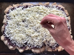 Hand putting shredded cheese on olive tapenade on flatbread for Olive & Pancetta Flatbread with mozzarella, mushrooms, and fresh basil. #flatbread #pizza #olives #tapenade #mediterranean #easydinner #dinner