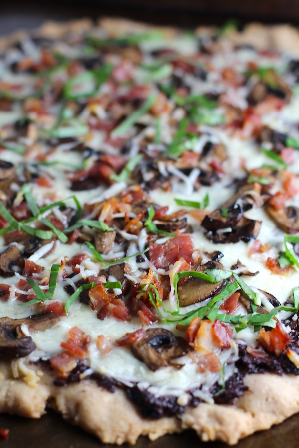Close up of Flatbread with crispy gluten free crust, salty and briny Olive Tapenade,  creamy mozzarella, earthy and meaty mushrooms, peppery pancetta, and fresh basil.  #flatbread #pizza #olives #tapenade #mediterranean #easydinner #dinner