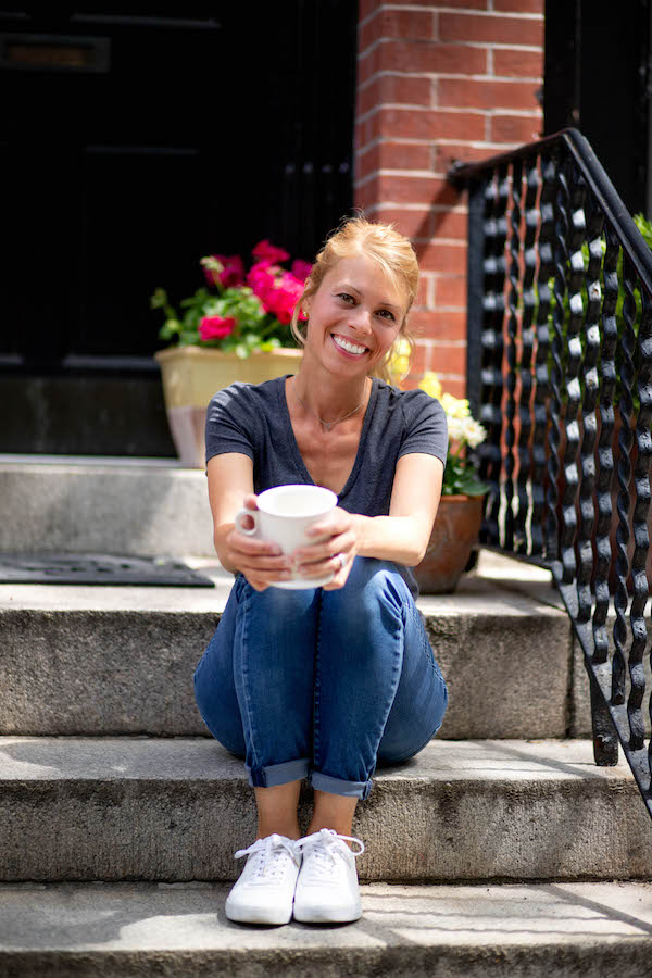 Carrie Tyler, food blogger behind www.talkingmeals.com, sitting on front stoop with coffee.
