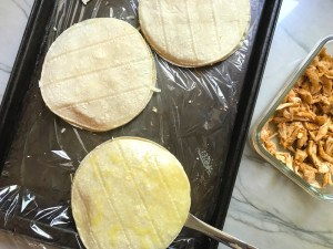 3 Tortillas assembled for Chicken Corn Tortilla Quesadillas. They have crispy edges, a soft gooey center, and are mouthwatering flavor. They have hearty shredded chicken flavored with warm and smoky Mexican spices. Then shredded Pepper Jack cheese and Cheddar is layered to get melty and oozy and delicious. It's an irresistible new easy dinner or appetizer idea. #quesadillas #mexicanfood #enchiladas #familydinner #chicken