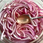 Slices of red onion with pickling liquid in bowl for Pickled Onions in a bowl soaking. They are tart, tangy, sweet, and savory.  They go on just about anything and are so unbelievably delicious, they can make a shoe taste good!  Best part, you can make a ton of them ahead!