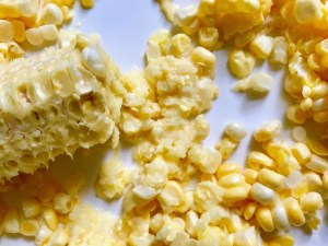 Kernels cut from a cob of corn for Chilled Golden Corn Soup with Turmeric.  Scallions on top for garnish. It's thick, creamy, silky and delicious. The entire family will love this easy stovetop corn soup! #summerfood #cornsoup #corn #vegetarian #vegetablerecipes #sides