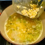 Adding corn kernels to scallions and broth in pot for Chilled Golden Corn Soup with Turmeric. Scallions on top for garnish. It's thick, creamy, silky and delicious. The entire family will love this easy stovetop corn soup! #summerfood #cornsoup #corn #vegetarian #vegetablerecipes #sides
