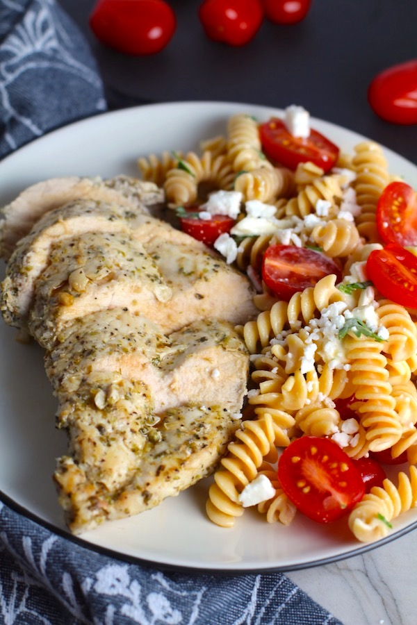Mediterranean Chicken sliced on plate with a tomato and feta pasta. This Mediterranean Marinade is only a few ingredients, can be made ahead, and is delicious!
