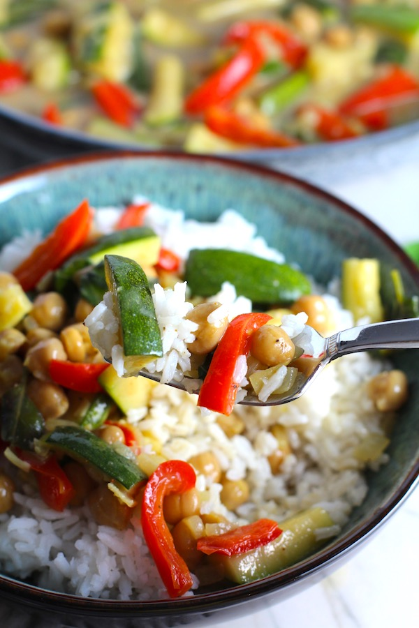 Family Chickpea Coconut Curry over rice in a bowl with fork holding a bite.  It has bell pepper, zucchini, onion, coconut milk, and warm Indian Curry spices.