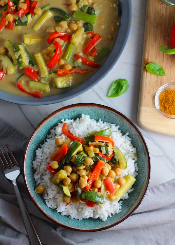 Family Chickpea Coconut Curry over rice in a bowl with red bell pepper, zucchini, onion, coconut milk, and warm Indian Curry spices.