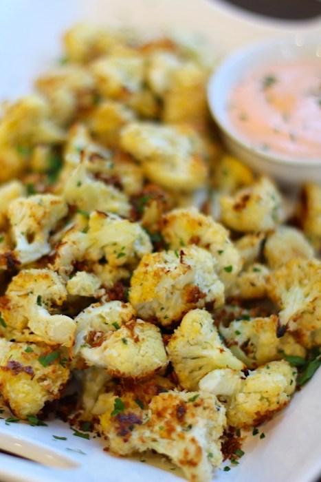 Baked Coconut Cauliflower Bites on plate with Sriracha Mayo dipping sauce.  They have a slightly sweet and salty crunch outside from the shredded coconut and panko mixture.  The inside is soft and creamy.  Dip in the Sriracha Mayo.  Baked, not fried, so healthy!  Easy to make, easy to eat! #cauliflowerrecipes #healthyrecipes #sidedishes #appetizers #healthysnacks