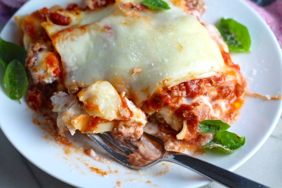 Lasagne on a plate with a fork cutting bite. from the dish. This Italian Sausage Lasagne Recipe is the stuff that dreams are made of.  Layers of pasta, creamy ricotta, salty chewy mozzarella, salty and hearty Italian Sausage, and sweet and tangy tomato sauce.