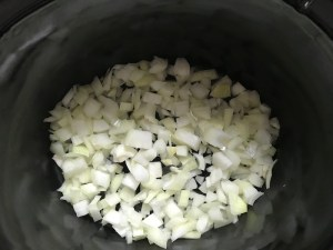 Diced onion in Slow Cooker insert for Smoky Pulled Beef Brisket.  It's smokey, savory, tender, moist, and full of flavor. In a delicious sauce, it goes great on a sandwich, over polenta, on rice, or potatoes. #slowcooker #crockpot #brisket #beefbrisket #pulledbeef #pulledpork