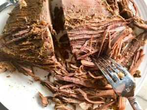 Fork shredding cooked brisket for Smoky Pulled Beef Brisket.  It's smokey, savory, tender, moist, and full of flavor. In a delicious sauce, it goes great on a sandwich, over polenta, on rice, or potatoes. #slowcooker #crockpot #brisket #beefbrisket #pulledbeef #pulledpork