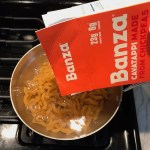 Pouring a box of Banza pasta into a pot of water for Chicken Stroganoff with mushrooms, and spinach. It has a thick, creamy, savory mushroom sauce with a touch of tangy sour cream. #chickendinners #chickenrecipes #familydinners #dinnerideas