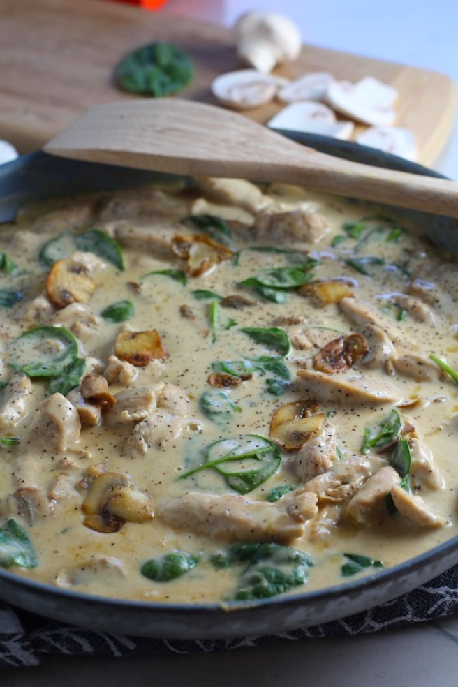 Chicken Stroganoff in a skillet with mushrooms and spinach.  It has a thick, creamy, savory mushroom sauce with a touch of tangy sour cream. #chickendinners #chickenrecipes #familydinners #dinnerideas