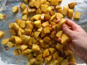 Hand rubbing seasoning on cut potatoes on sheet pan for Patatas Bravas with chorizo and creamy Paprika aioli.  This Patatas Bravas Recipe, or Spicy Potatoes, is easy, indulgent, and utterly delicious!  #potatorecipes #potatoes #potatosidedishes #patatasbravas #skilletpotatoes #sidedishes #chorizo