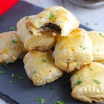 Mini Beef Wellington Bites stacked on platter. They are flaky and buttery on the outside. Puff Pastry is filled with a creamy mushroom and parmesan filling and tender beef filet.  #appetizers #partyfood
