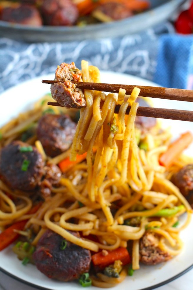 Chopsticks with bite of Teriyaki Meatballs with Veggie Stir Fry, and rice noodles on a plate. #asianmeatballs #teriyaki #noodles #familydinner #easydinners #dinnerideas