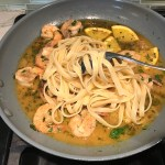 Pasta added to Shrimp and orange sauce in skillet for the Orange Brown Butter Shrimp Pasta Recipe. #shrimprecipes #shrimppasta #easydinners #dinnerideas
