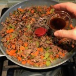 Beef filling in pan for Cottage Pie recipe. It has Spanish Chorizo and ground beef cooked in a rich and savory gravy with veggies and herbs.  Creamy mashed potatoes sit on top with manchego, parmesan, and garlic. #dinnerideas #cottagepie #shepherdspie