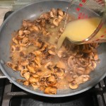 Adding broth to cooked sliced Mushrooms in skillet for this Heavenly Mushroom Sauce Recipe. #vegetarian #healthydinner #dinnerideas #mushrooms