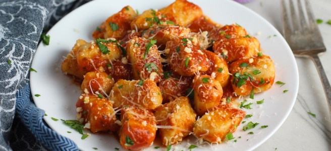 Cauliflower Gnocchi in tomato sauce on plate with parmesan and parsley. They are soft, silky, buttery, and melt-in-your-mouth! Made with cauliflower, they're a healthier version to traditional gnocchi! Add my simple Garlic Butter Sauce or Tomato Sauce and they are heaven.  #dinnerideas #gnocchi #cauliflower