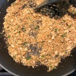 Cracker crumbs and parsley in pan for Bacon Mac and Cheese. It has a creamy and cheesy sauce with a touch of smokiness from the bacon, coats each piece of pasta.  On top, crispy crunchy, indulgent bacon fat cracker crumbs!