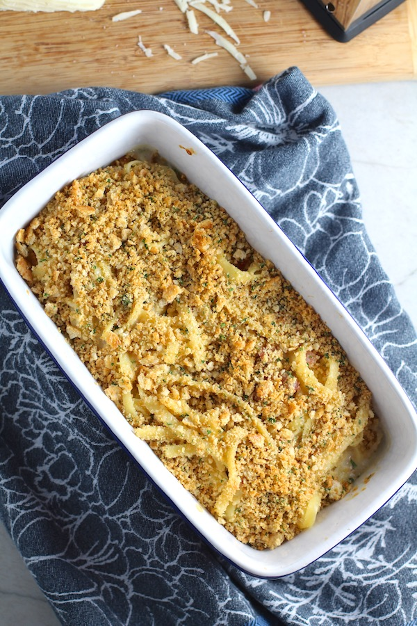 Bacon Mac and Cheese in baking dish. It has a creamy and cheesy sauce with a touch of smokiness from the bacon, coats each piece of pasta.  On top, crispy crunchy, indulgent bacon fat cracker crumbs!